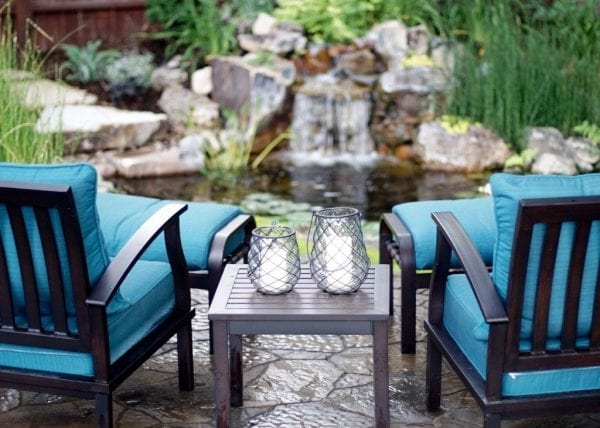 Beautiful, natural-looking pond in background with patio chairs and drinking glasses in front