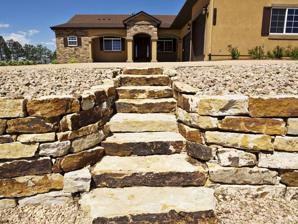 Retaining walls and stone stairs for front entrance of this home
