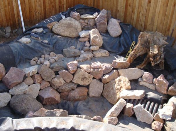 Beginning to add rocks and gravel to a pond