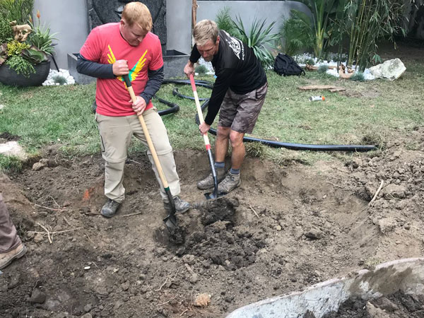 Two people digging a koi pond