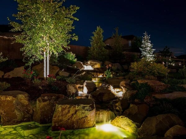 Landscape lighting fixtures in and around a water feature